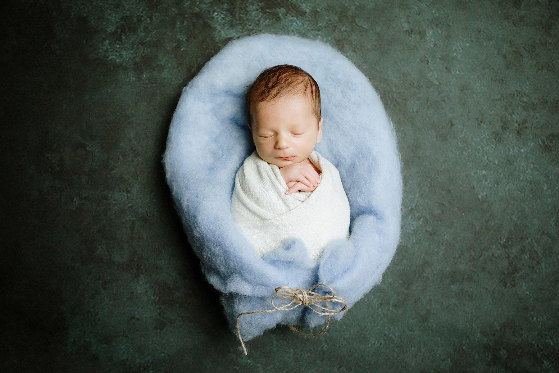 neonato fasciato e fotografato durante una sessione Newborn