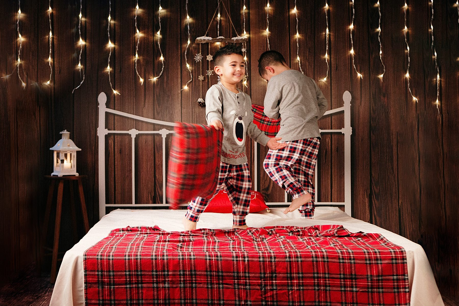 bambini che saltano sul letto durante servizio fotografico di natale