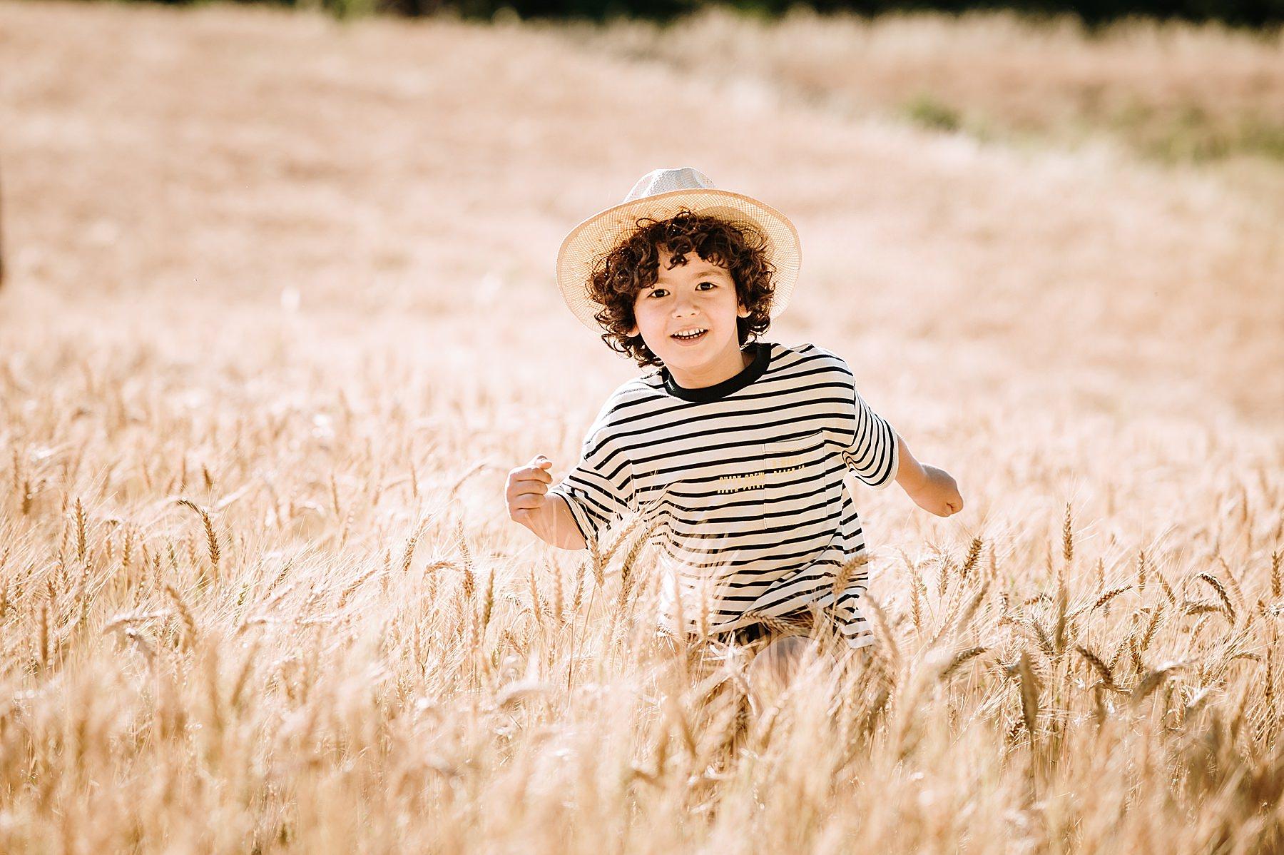 bambino che corre felice nel grano